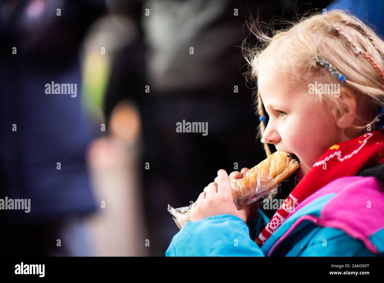 Une jolie petite fille bénéficie d'une saucisse chaude à un match de football de Stoke City FC, BET 365 Stadium Banque D'Images