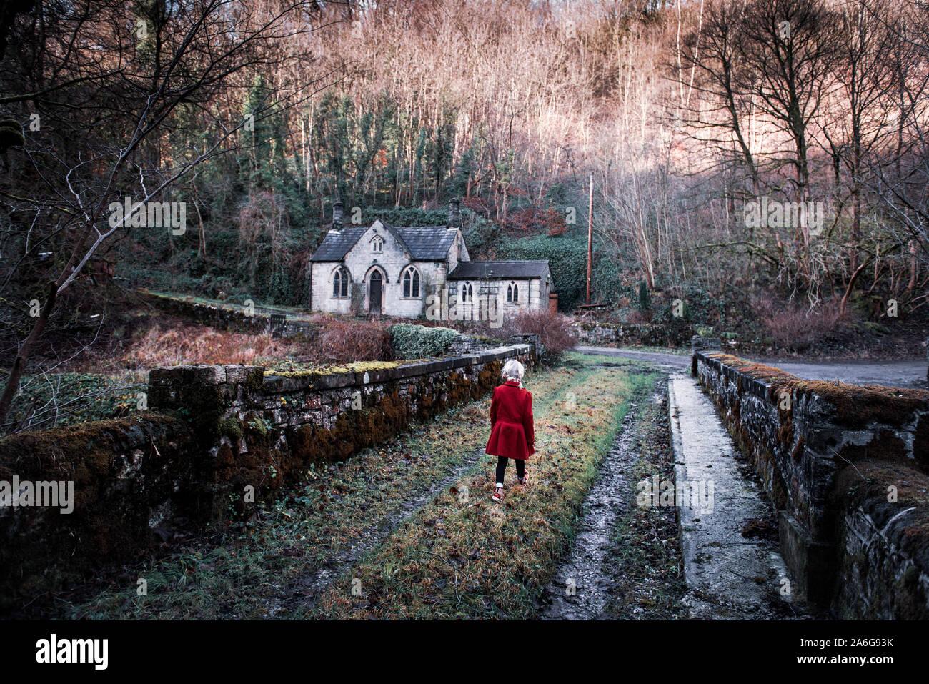 Une petite fille qui marche vers une vieille maison abandonnée, spooky effrayant, de l'église dans les bois, situé dans le Derbyshire Peak District National Park, hallow Banque D'Images