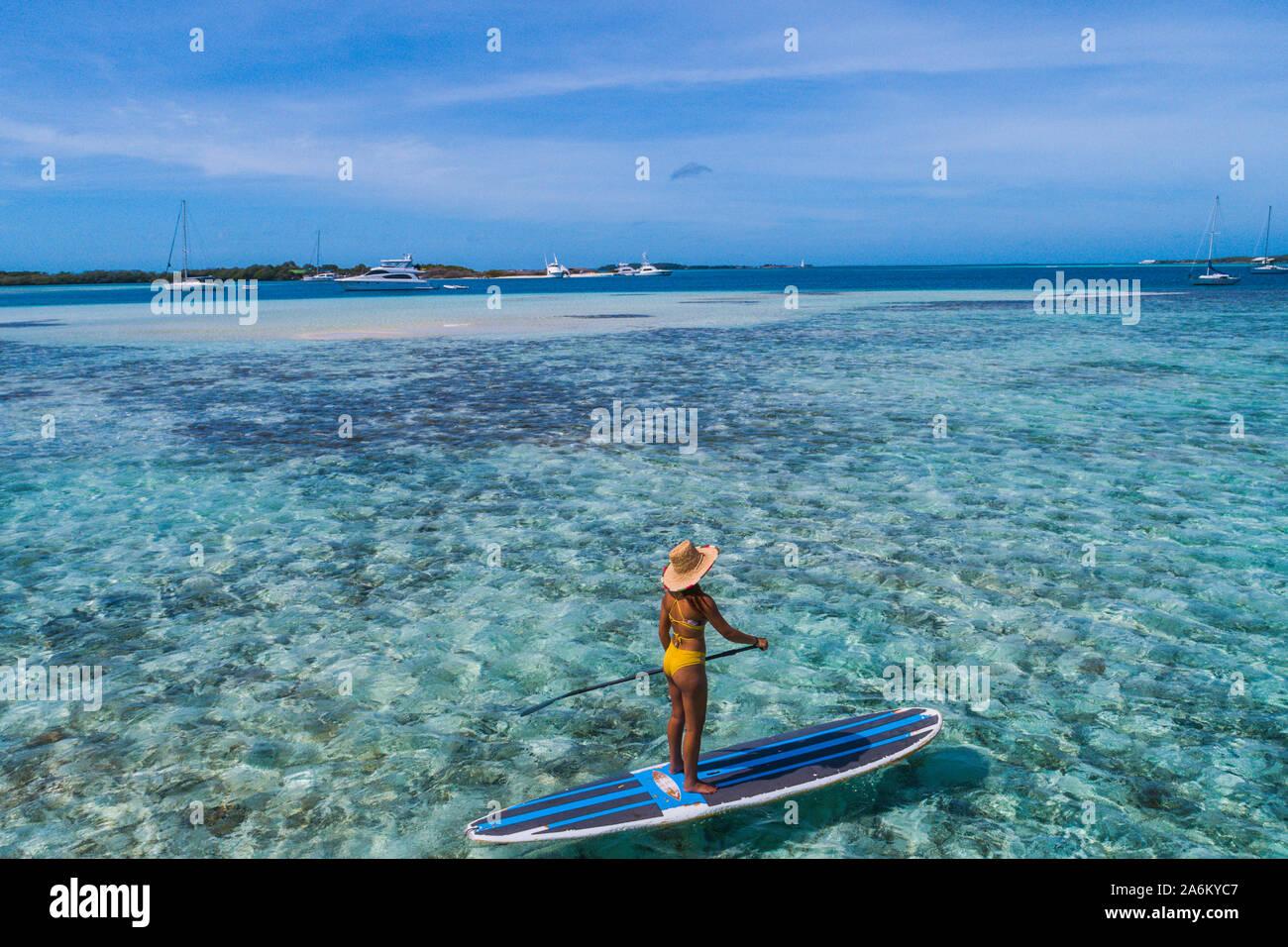 Drone aérien bird's eye view photo de jeune femme pratiquant ou sup paddle board in tropical Caribbean sapphire crystal clear eaux calmes Banque D'Images