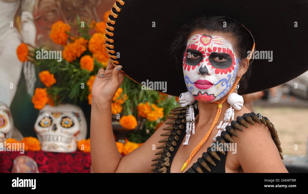 Jeune femme portant un crâne en sucre et immense sombrero à Dia de los Muertos événement à Mission San Luis Rey. Banque D'Images