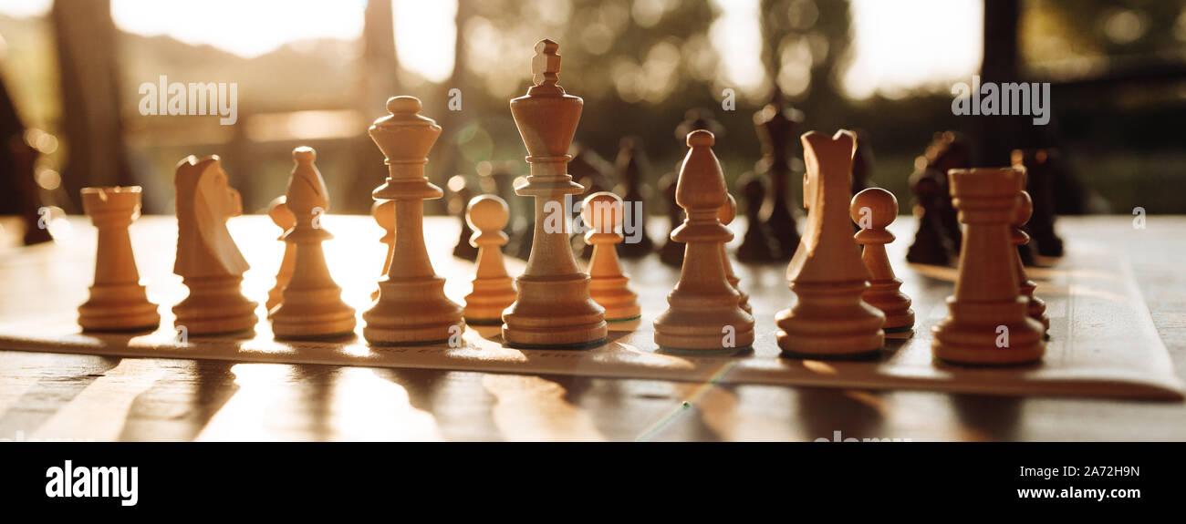 Jouer aux échecs sur un échiquier au coucher du soleil. La tactique et la stratégie. Figures en noir et blanc. Banque D'Images