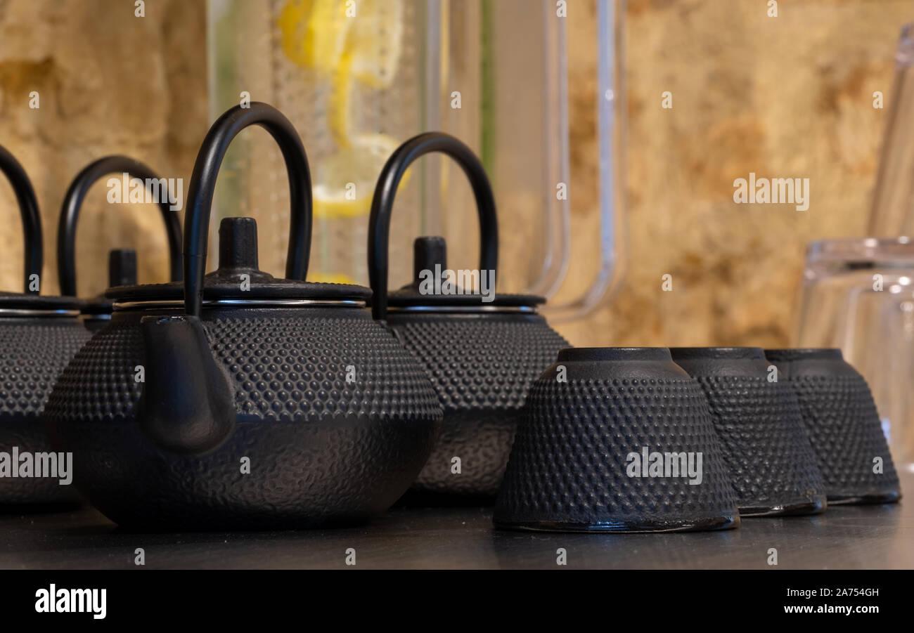 Close up of black fonte texturée théières de style asiatique avec des poignées et des tasses. Banque D'Images