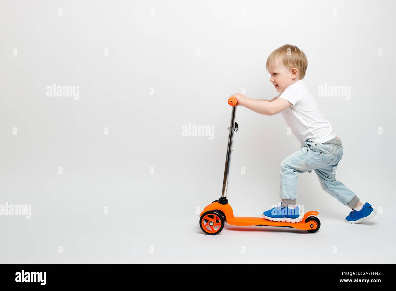 Heureux tout-petit enfant dans une orange en jeans scooter sur un fond blanc dans le studio. La publicité pour les jouets pour enfants avec l'espace pour le texte. Banque D'Images