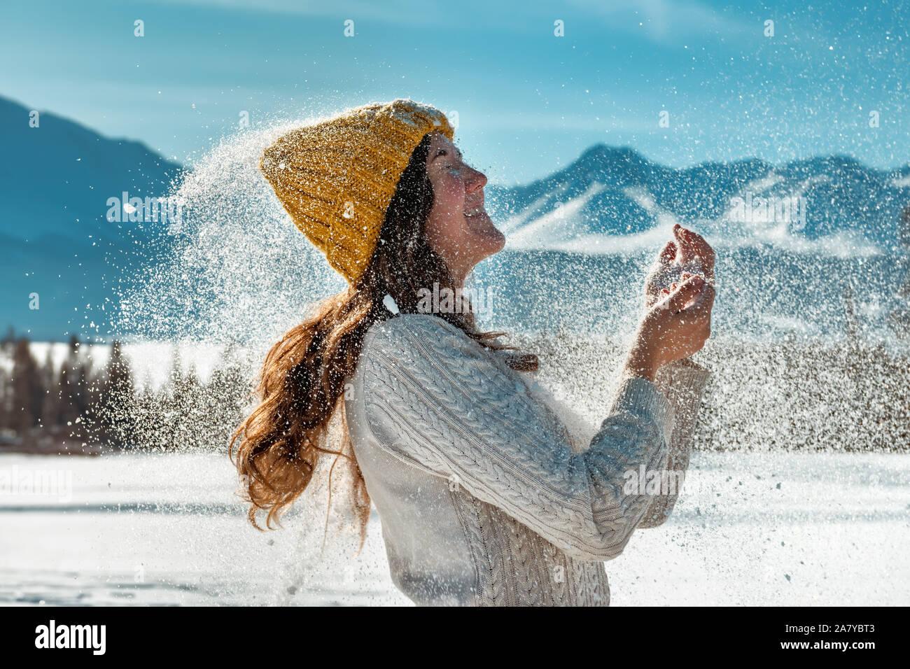 Happy girl joue avec poudre de neige contre forêt et montagnes Banque D'Images