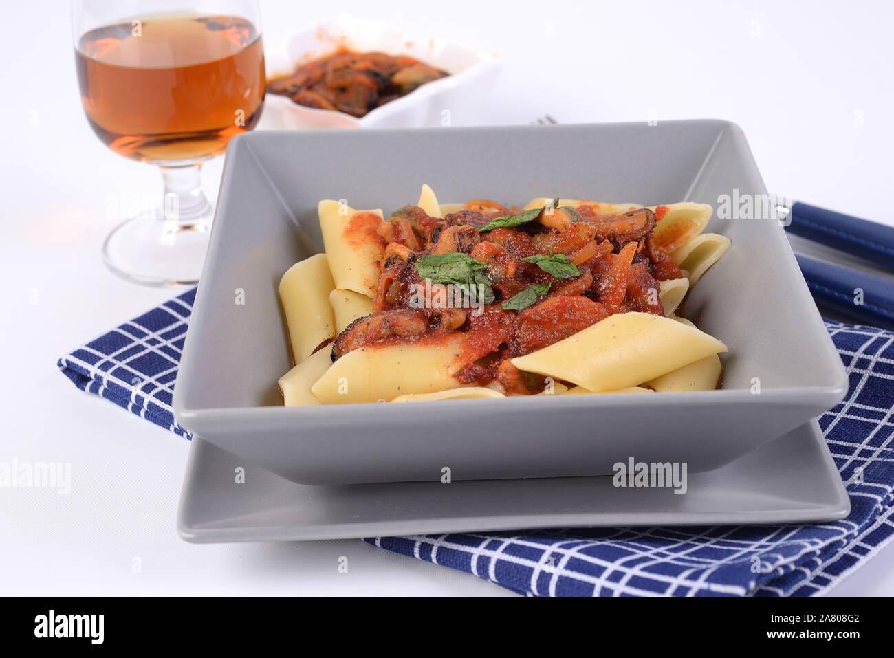 Pâtes Pennoni sauce avec des moules sur la plaque à fond blanc Banque D'Images