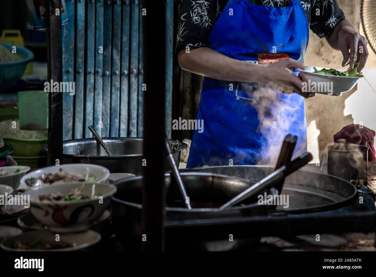 Bangkok, Thaïlande - 27 Oct 2019: Chef de nouilles aux oeufs avec le porc rôti dans un restaurant local, Thaïlande. L'alimentation de rue dans un traditionnel de nouilles faire Banque D'Images