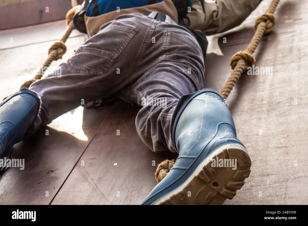 Jeune garçon de wellys escalade un mur avec des cordes. Banque D'Images