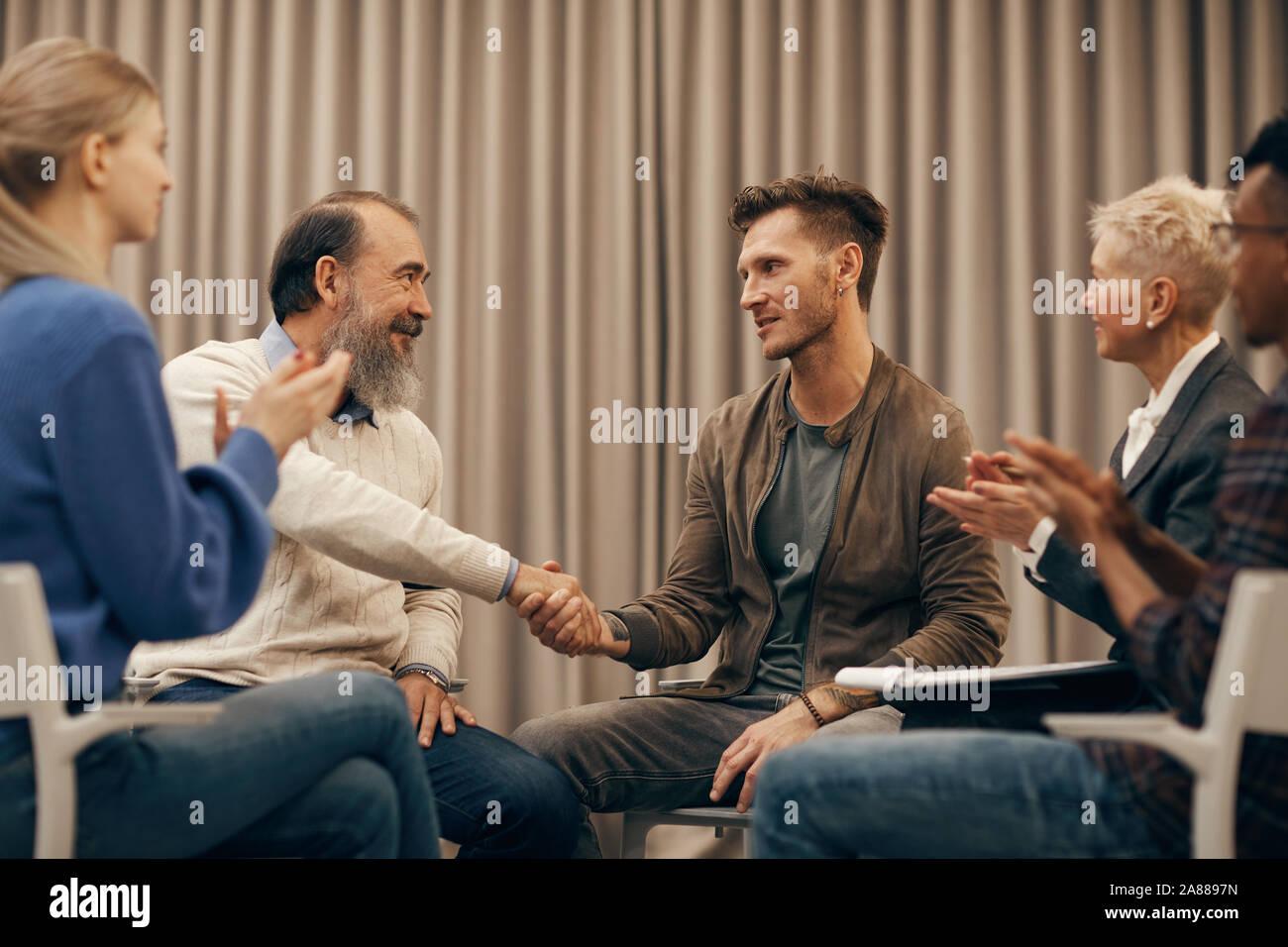 Deux hommes assis et serrer la main à l'autre tandis que d'autres personnes frappant des mains ils chaque message d'autres Banque D'Images