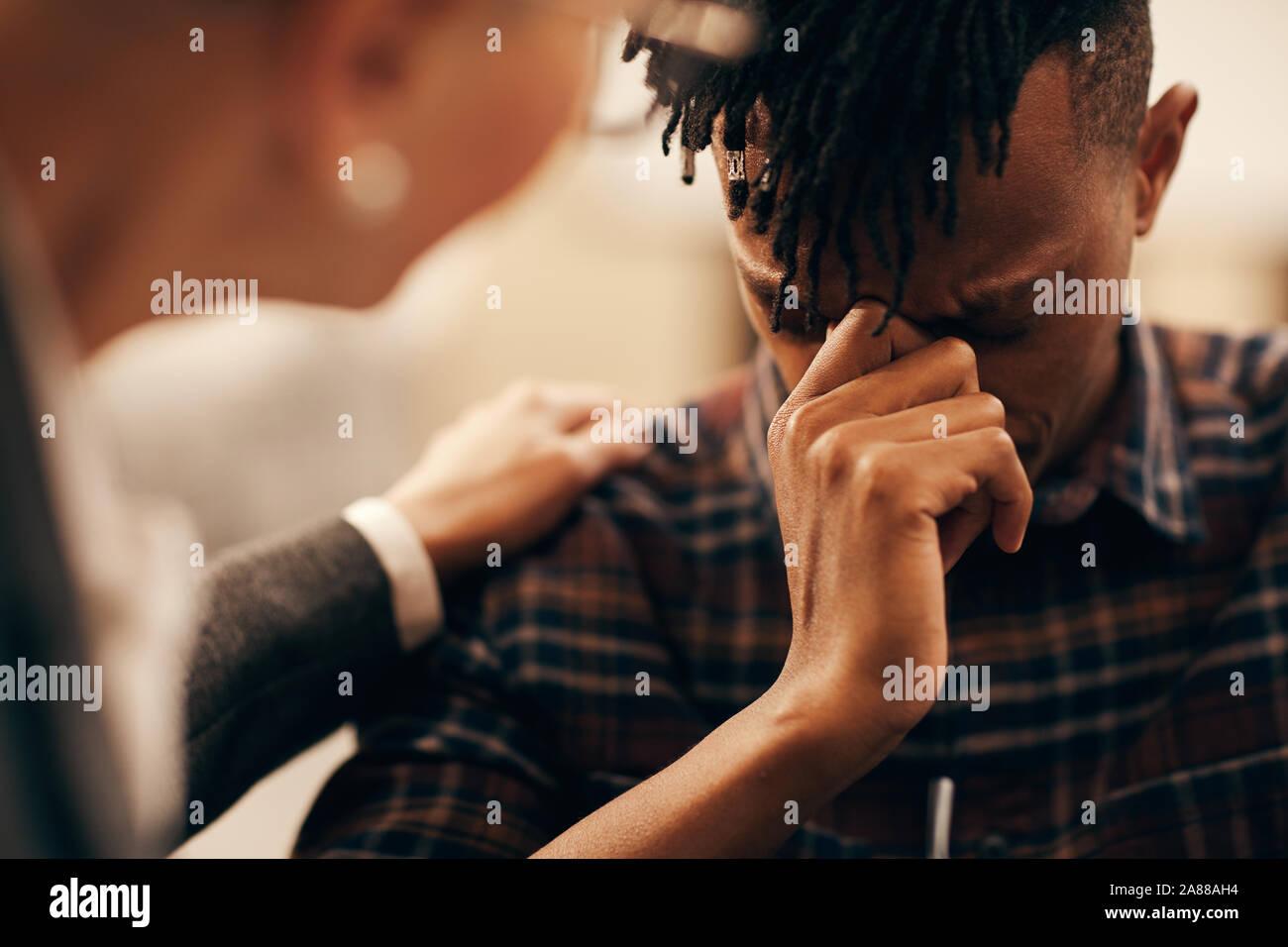 Jeune homme africain inquiète de son problème et de dire à ce sujet à la femme qui le réconforter Banque D'Images