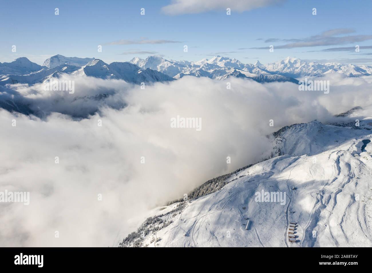 Vue aérienne d'une forêt couverte de neige fraîche et nuages dans le domaine d'Aletsch Arena. La Suisse à l'automne Banque D'Images