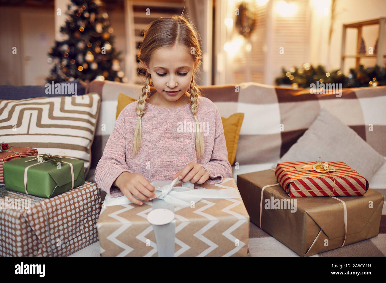 Petite fille assise sur le canapé et l'ouverture de gros cadeau de Noël qu'elle l'obtenant de Père Noël pour Noël à la maison Banque D'Images