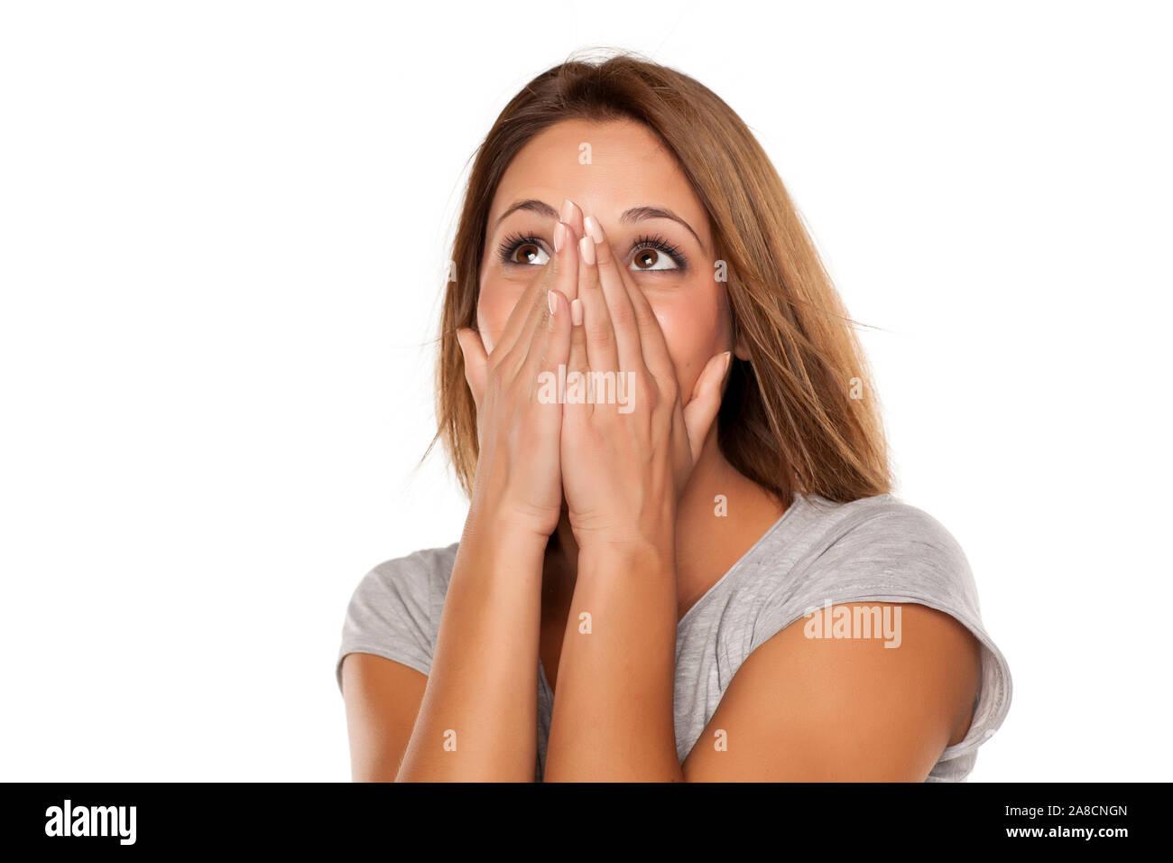 Jeune femme couvre son visage avec ses mains Banque D'Images