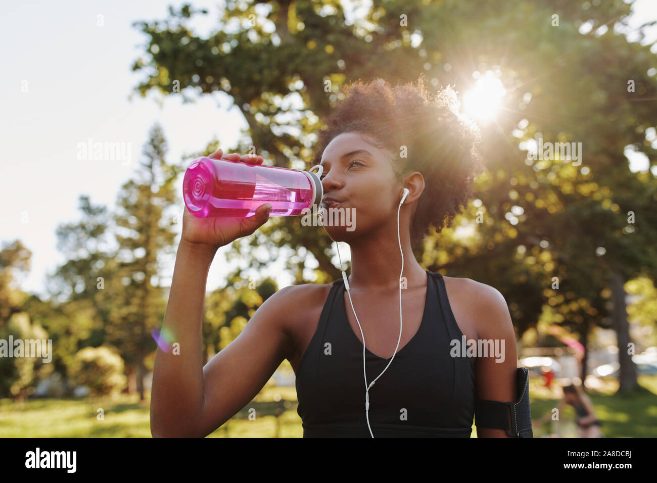 Athlète Fitness young african american woman listening to music on earphones l'eau potable dans une bouteille d'eau réutilisable après l'entraînement sur l'exercice Banque D'Images