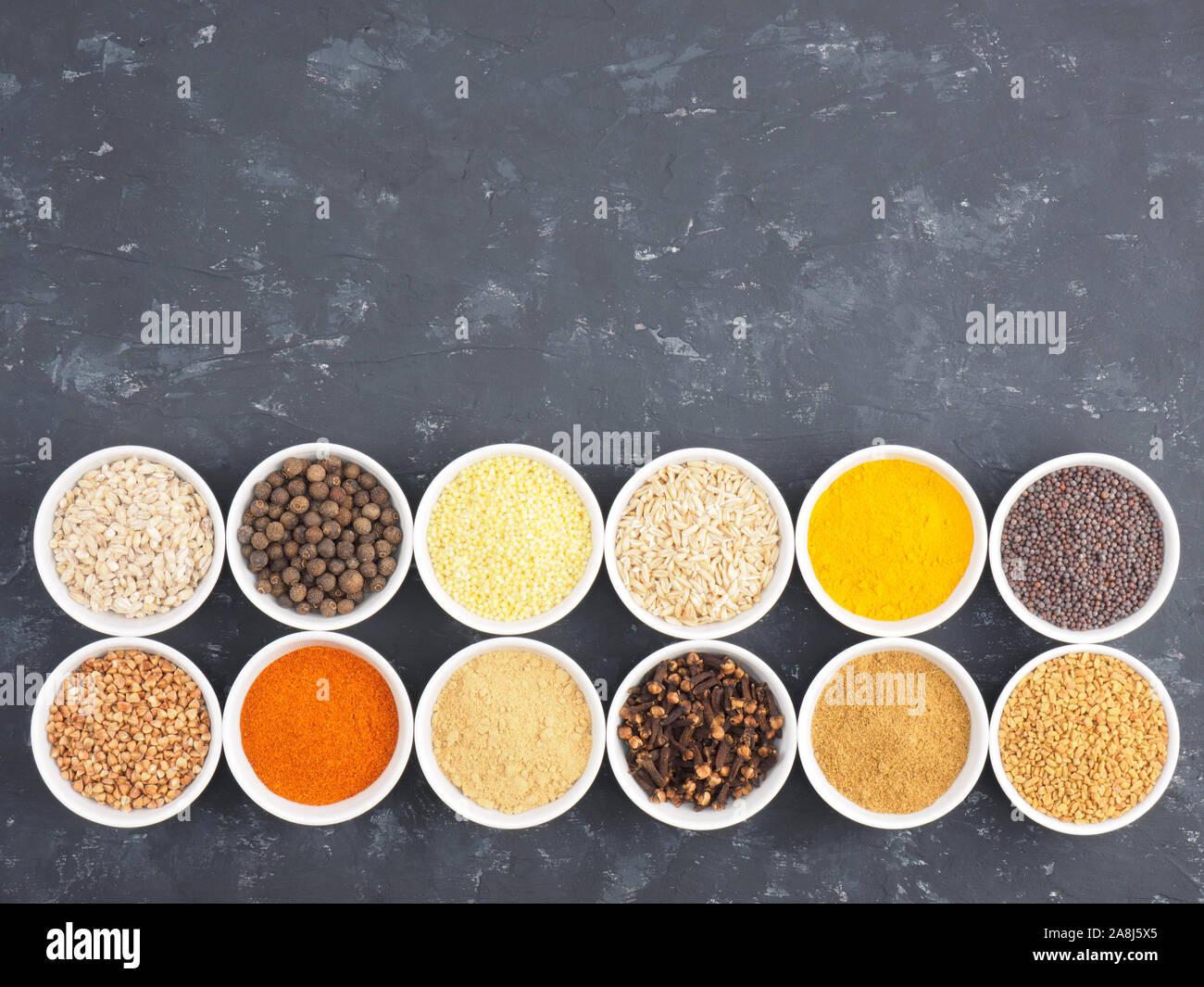 Le sarrasin, le millet, le piment, le fenouil, l'avoine, le poivre piment, masala, fenugrec, girofle, curcuma, cumin, graines de moutarde, la cardamome verte en blanc bols sur bl Banque D'Images
