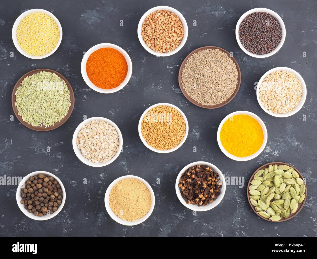 Le sarrasin, le millet, le piment, le fenouil, l'avoine, le poivre piment, masala, fenugrec, girofle, curcuma, cumin, graines de moutarde, de la cardamome verte sur béton noir ba Banque D'Images