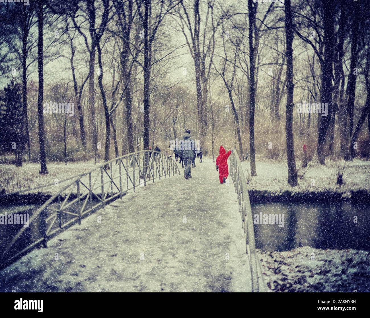 Décembre à Munich: bruine de neige à l'Englischer Garten, personnes et un enfant avec combinaison de saut rouge faire une promenade dans le parc Banque D'Images
