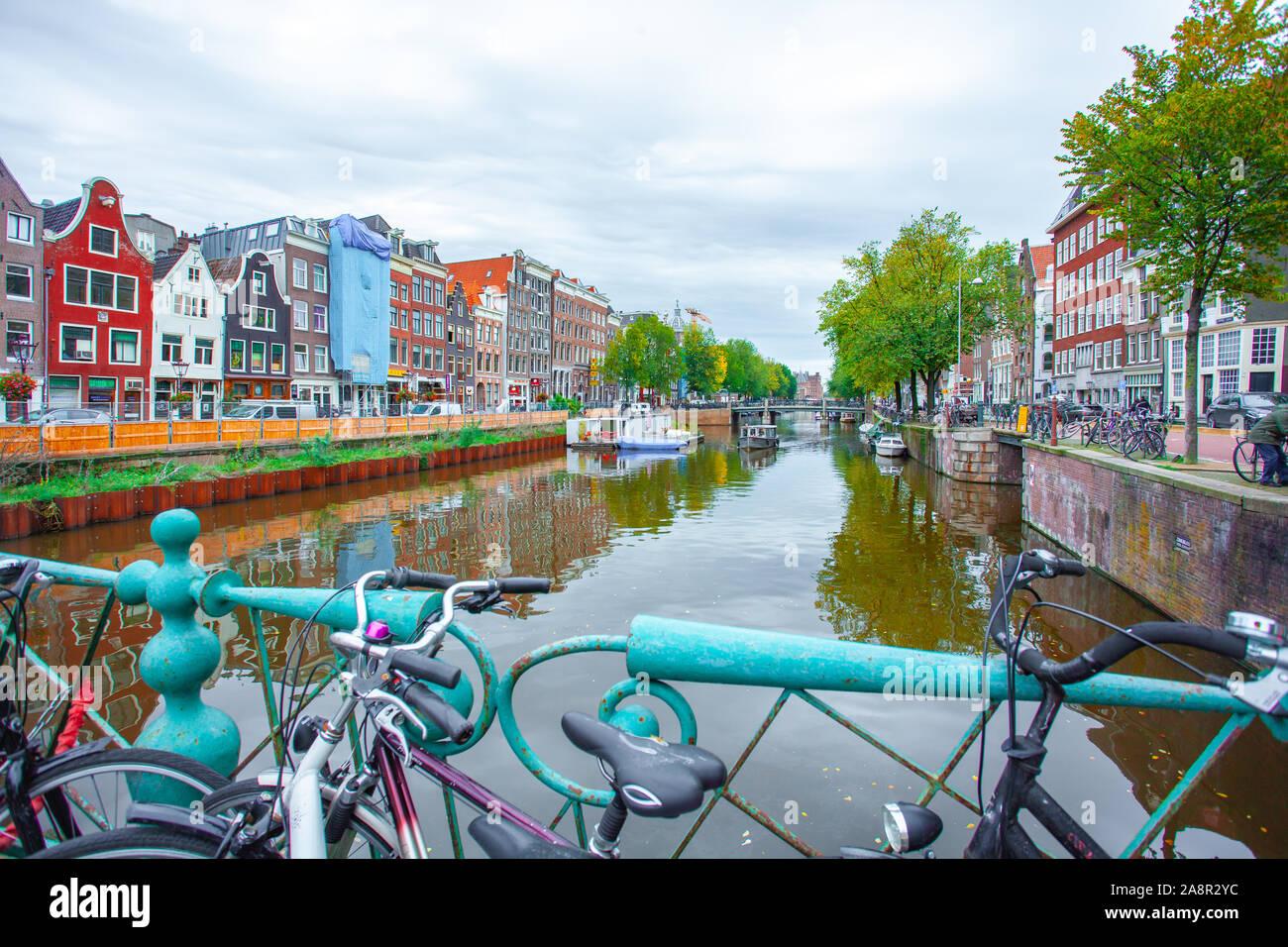 Amsterdam, Nethertlands - 14.10.2019: Des vélos sur un pont sur les canaux d'Amsterdam. Maisons colorées et de fleurs. De l'automne. Les voyages. Banque D'Images