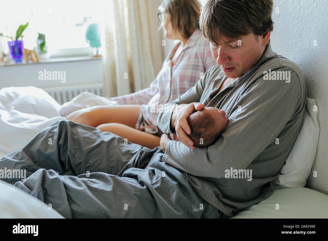 Père avec bébé au lit, woman on background Banque D'Images