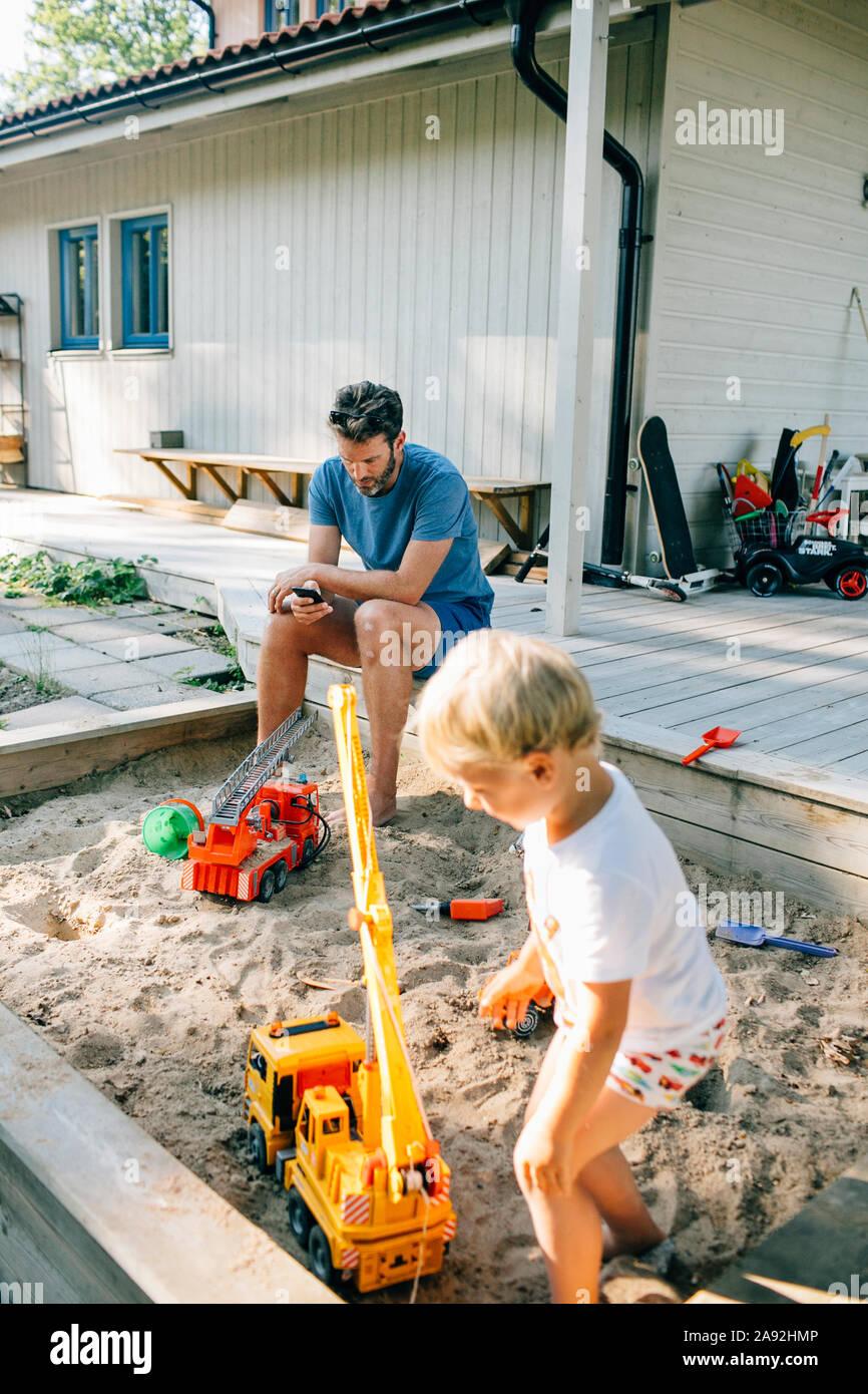 Fille jouant dans un bac à sable Banque D'Images