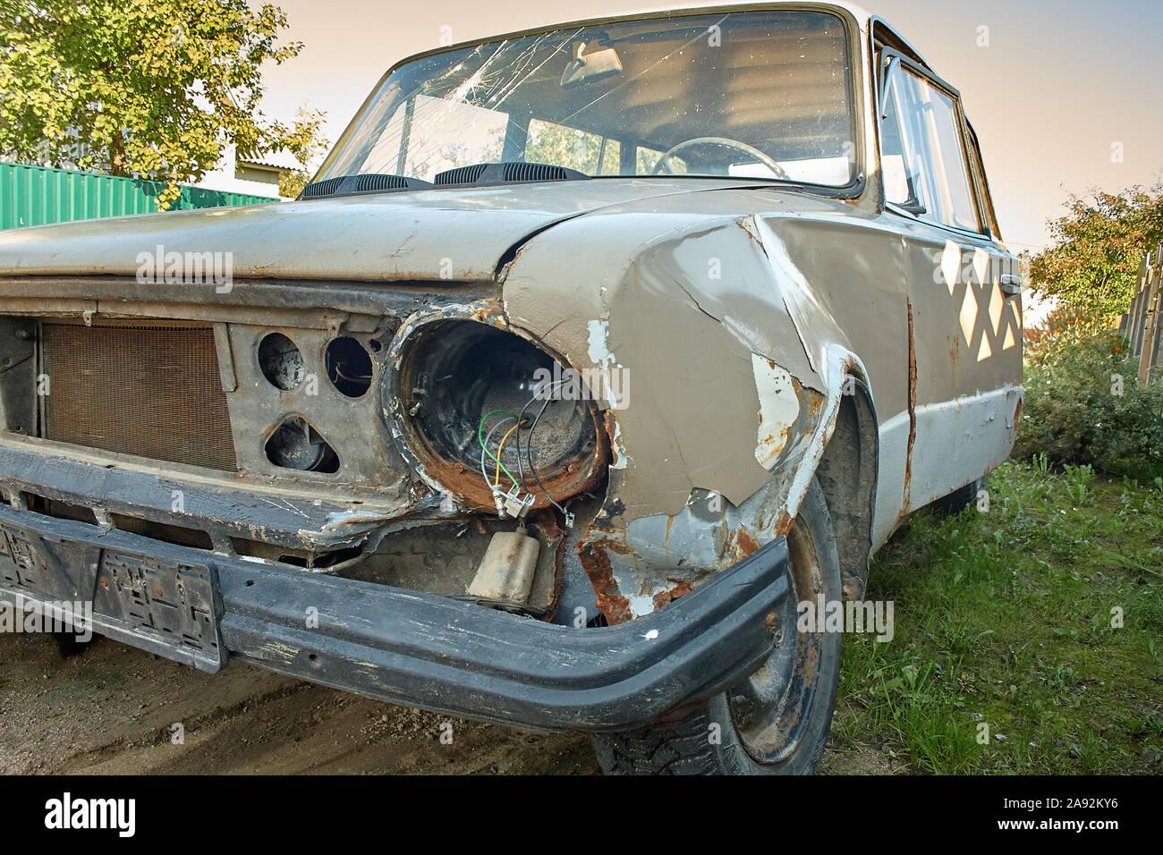 Vieille voiture accidentée dans un style vintage. Libre vue avant phares des épaves rouillées voiture abandonnée sur l'arrière-plan flou arbre vert . Banque D'Images