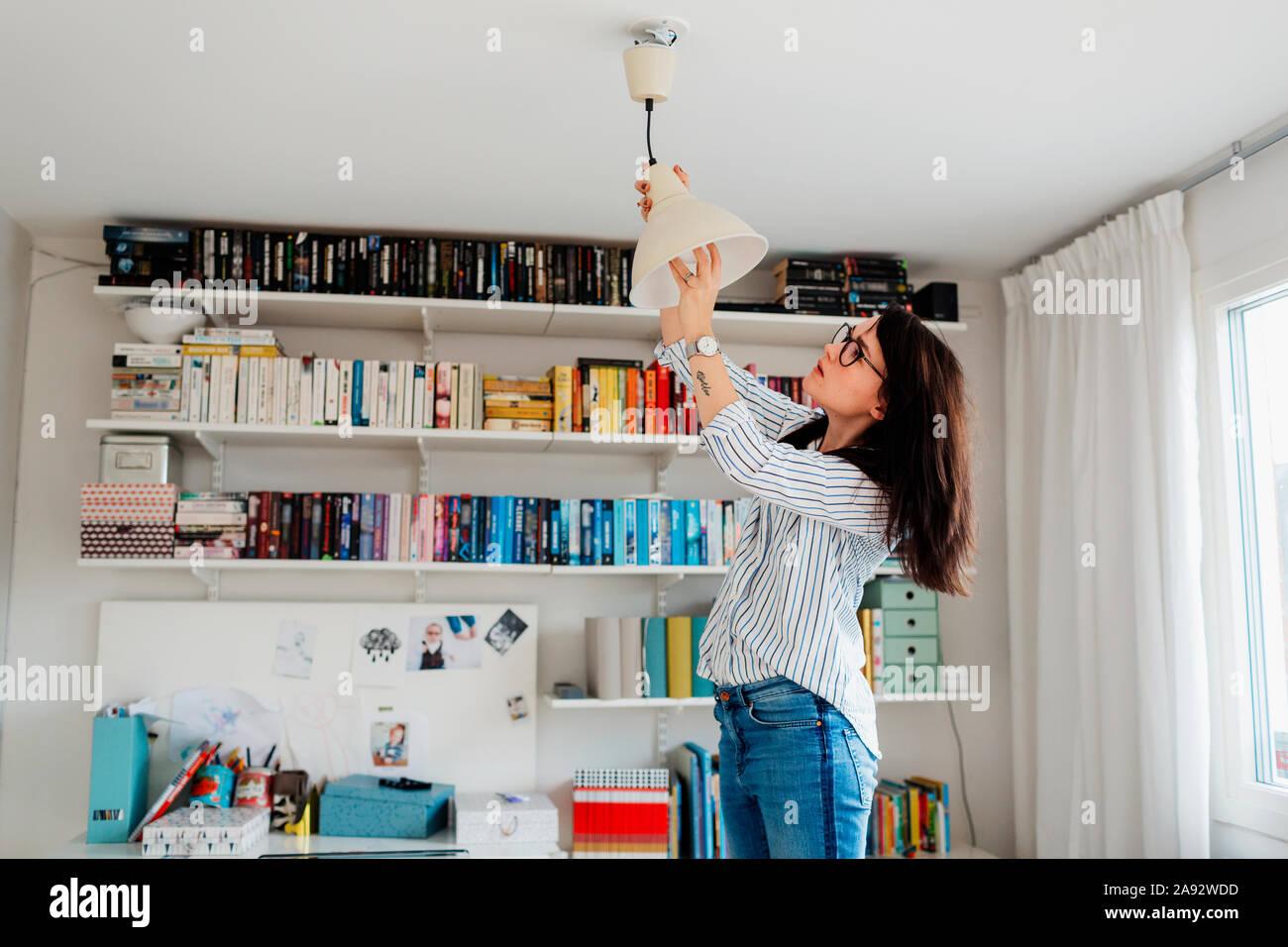 Femme de changer l'ampoule en chambre Banque D'Images