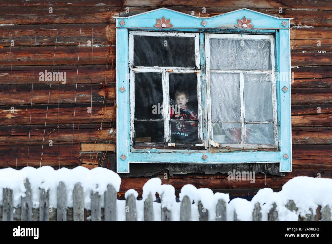 La Russie. 08Th Nov, 2019. La région de Kemerovo, Russie - 4 novembre, 2019: un garçon à la recherche d'une fenêtre d'une maison en bois dans le village reculé de Kilinsk. Selon le recensement de 2010, 200 personnes vivent dans le village, la plupart d'entre eux priestless des vieux croyants. Alexander Ryumin/crédit: TASS ITAR-TASS News Agency/Alamy Live News Banque D'Images