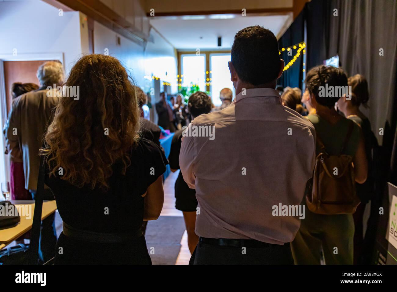 L'arrière du grand groupe de personnes à la recherche de quelque chose en face d'eux tout en ayant une grande réunion du congrès Banque D'Images