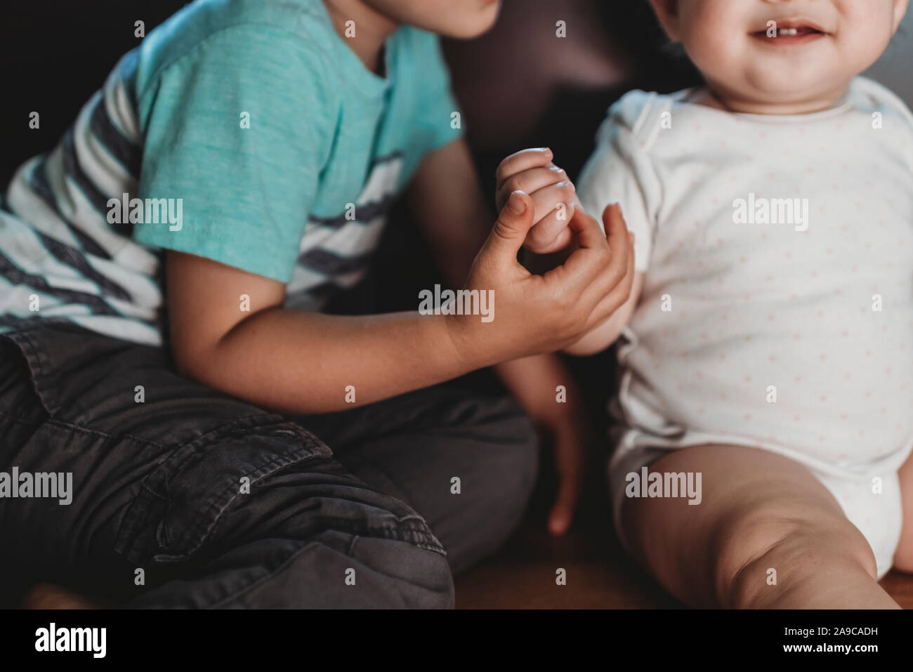 Big brother holding hand of smiling baby sister polkadot Onesie Banque D'Images