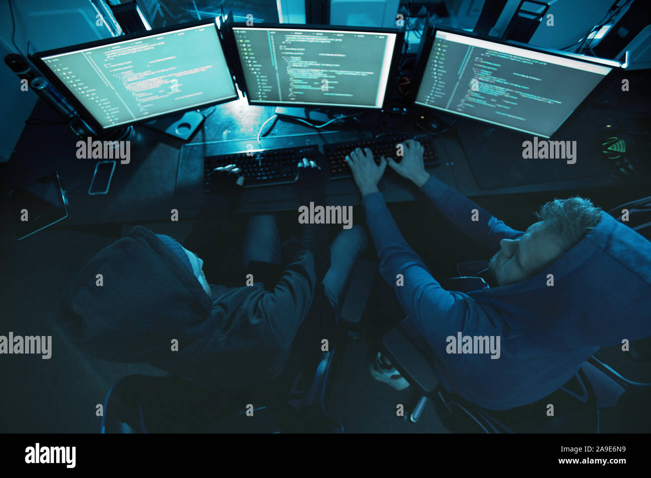 Vue arrière de pirates informatiques assis devant des écrans d'ordinateur et en tapant ils briser le système et de travailler en équipe Banque D'Images