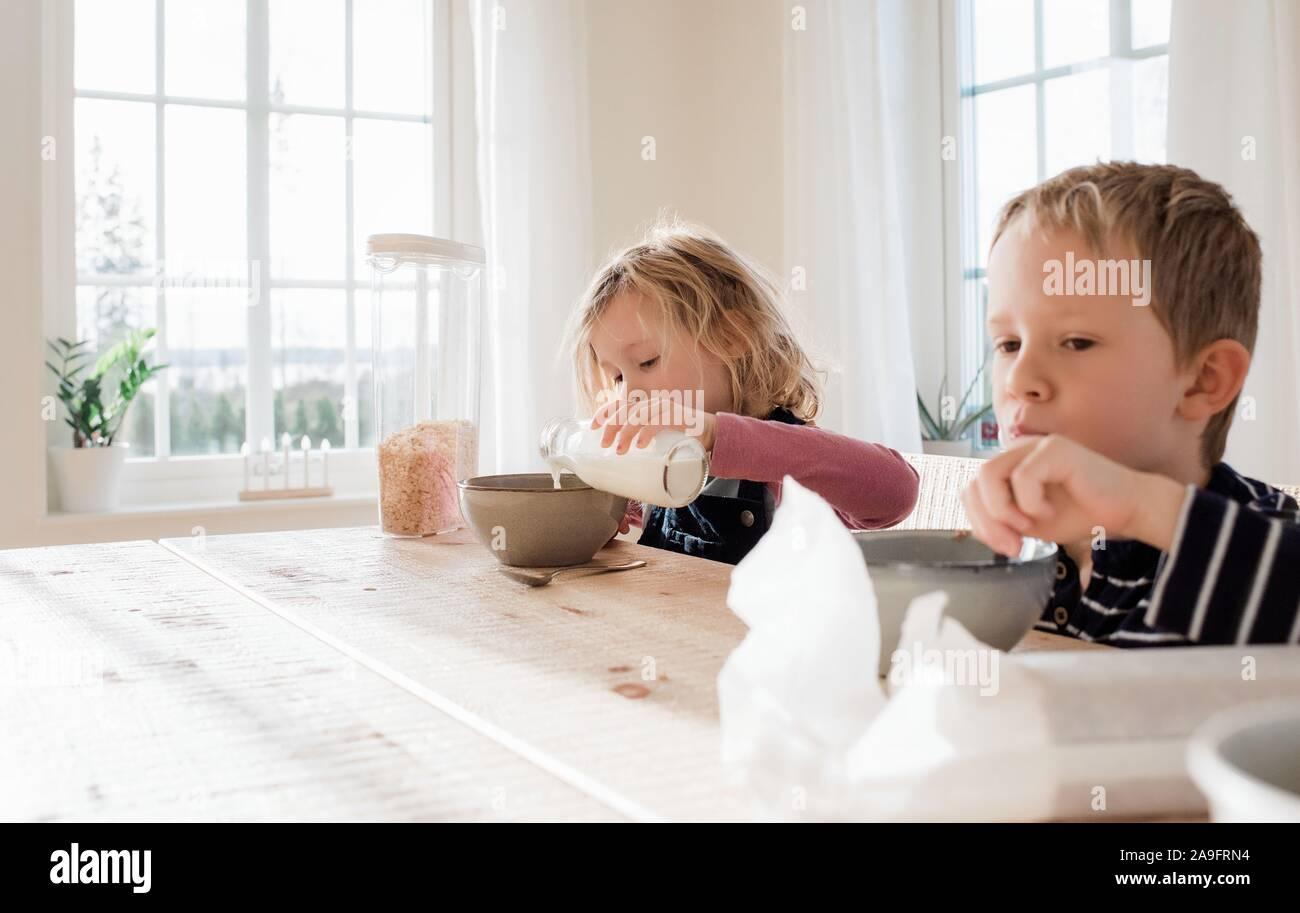 Frère et sœur manger le petit déjeuner à la maison avant l'école Banque D'Images
