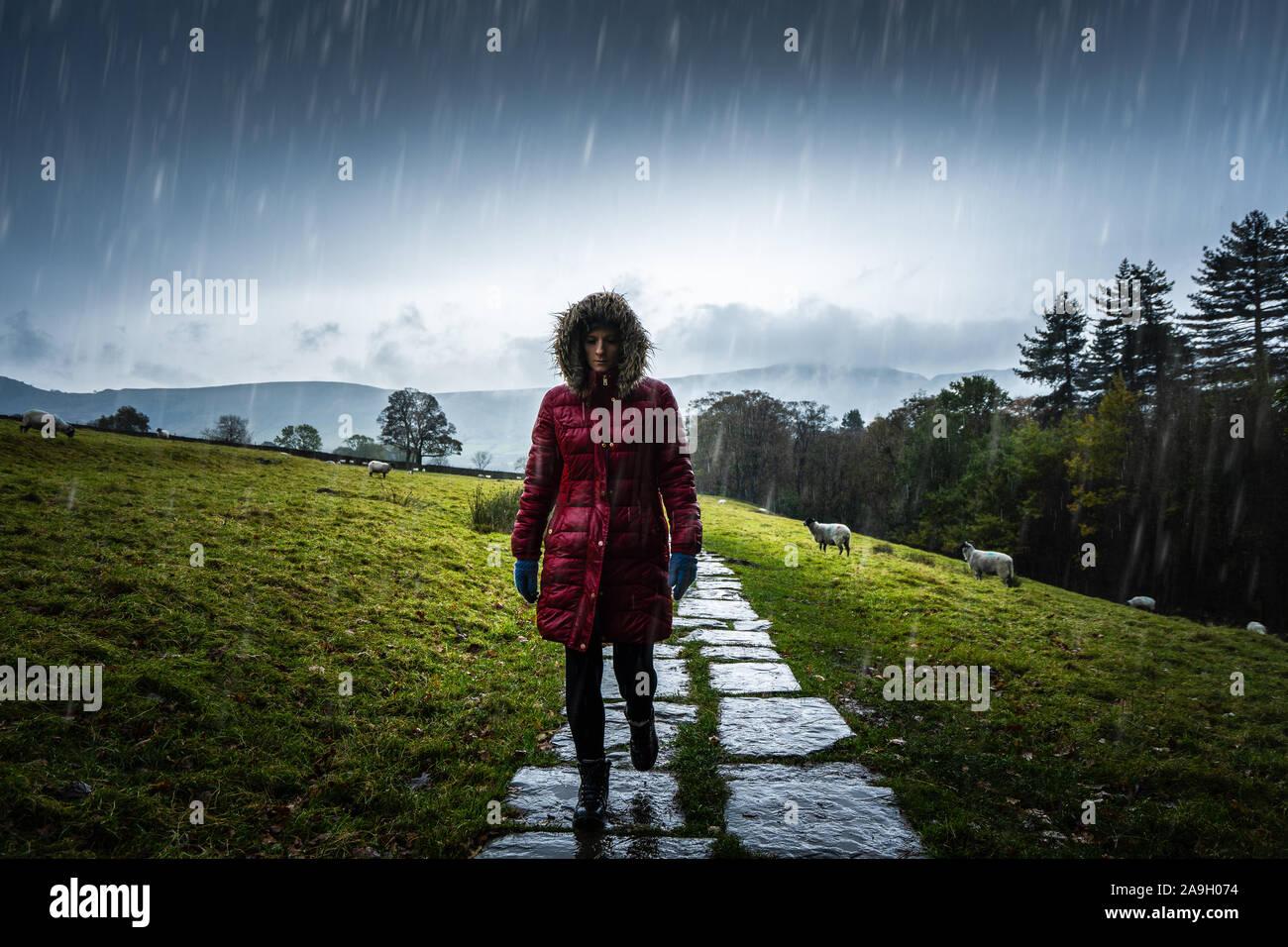 Une jeune femme, randonneur, l'ascension d'une montagne à l'hiver froid pluie dans le Derbyshire Peak District National Park, saison d'hiver dans la campagne britannique Banque D'Images