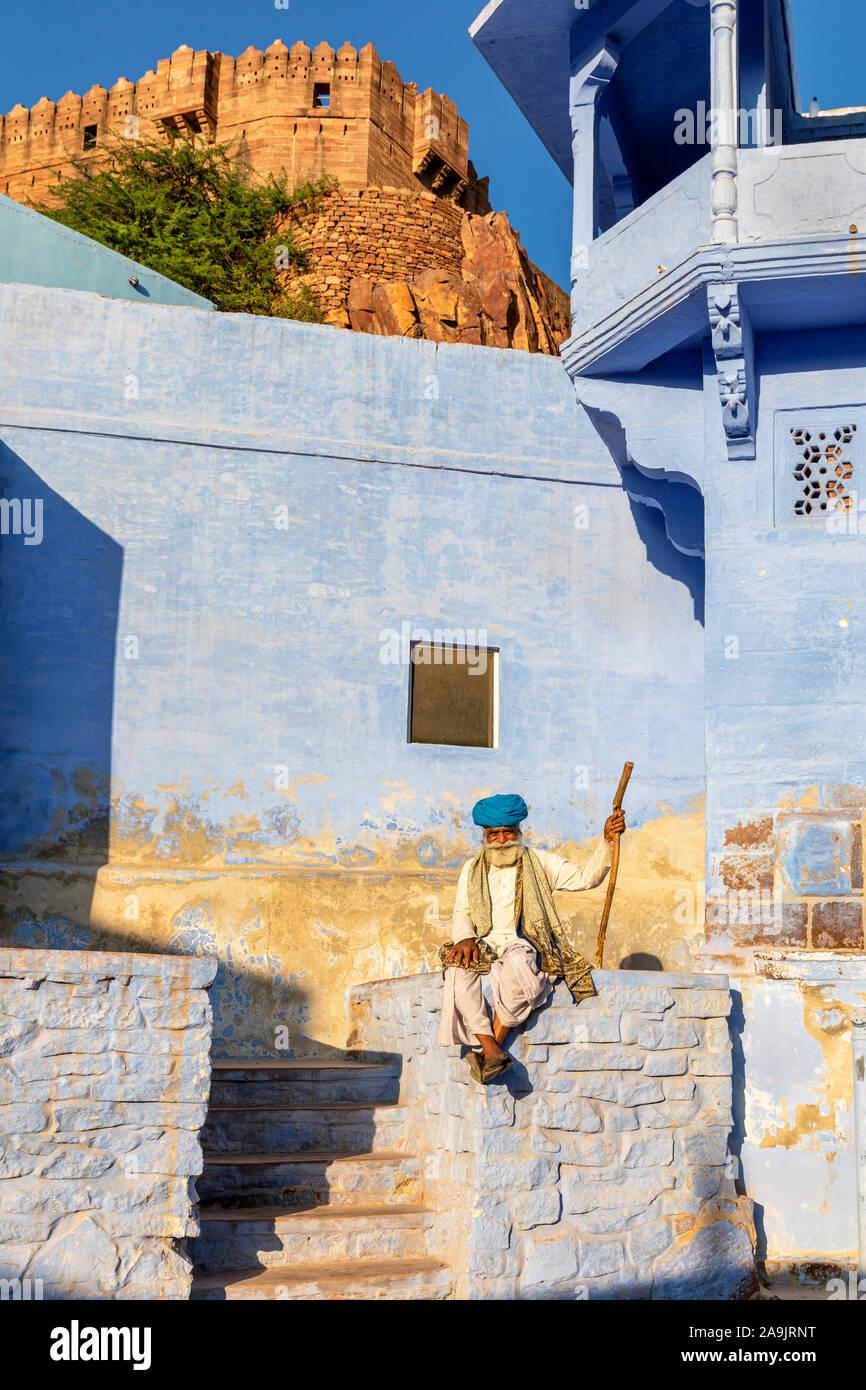Un homme âgé se reposant dans la ville bleue de Jodhpur avec Mehrangarh Fort en arrière-plan, Jodhpur, Rajasthan, India Banque D'Images