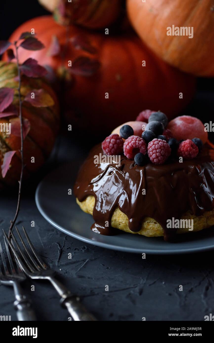 Dessert maison saine. Pouding vapeur traditionnel avec lustre de chocolat et de baies et les courges d'hiver sur fond noir copy space Banque D'Images