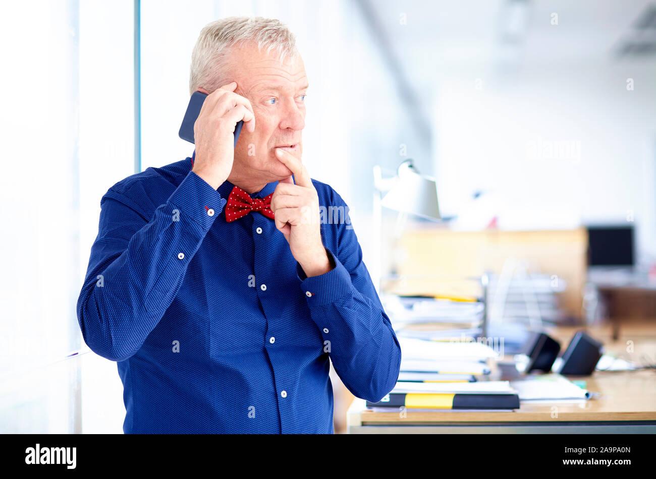 Senior businessman à thoughfully alors qu'il était assis dans le bureau et de passer un appel téléphonique. Banque D'Images