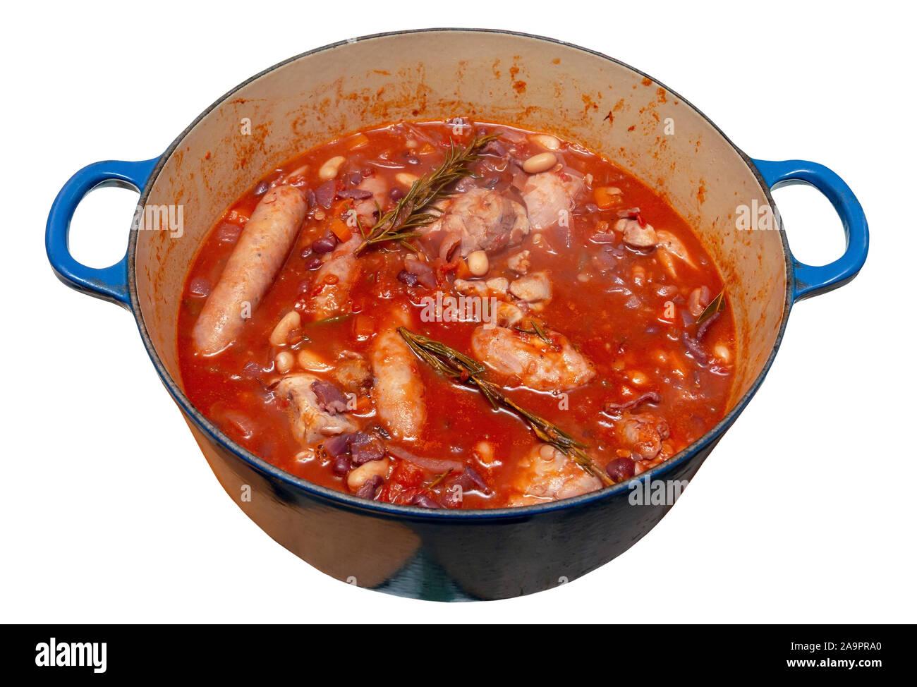 Poulet, saucisses, bacon et haricots cassoulet dans un grand pan bleu sur un fond blanc isolé Banque D'Images