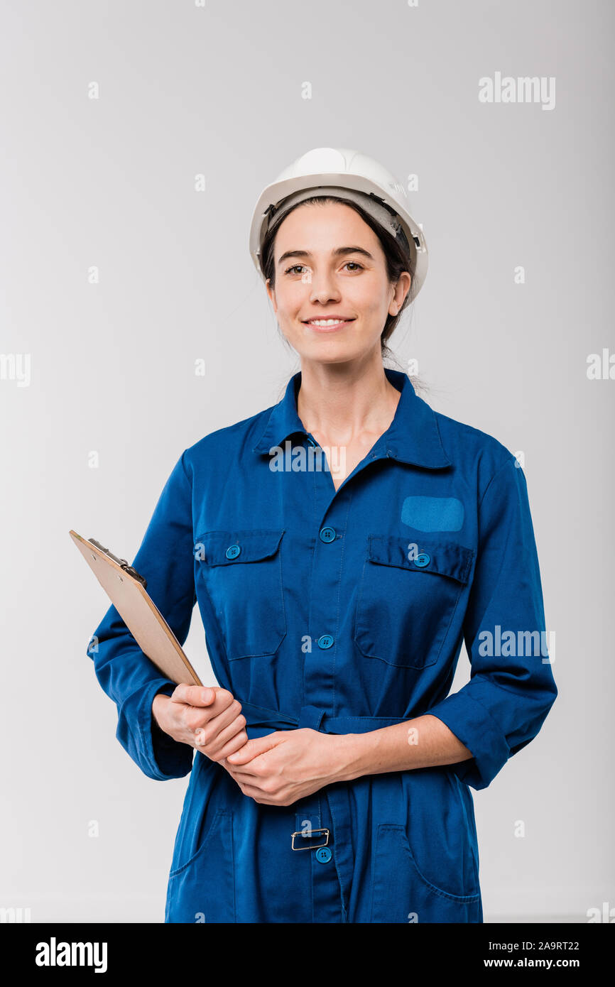Happy young female mechanic workwear en bleu et casque holding clipboard Banque D'Images