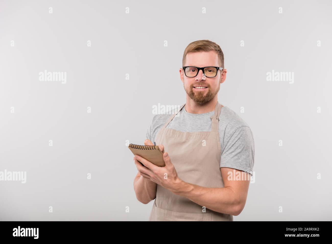 Happy young bearded waiter writing down ordre de client dans le bloc-notes Banque D'Images