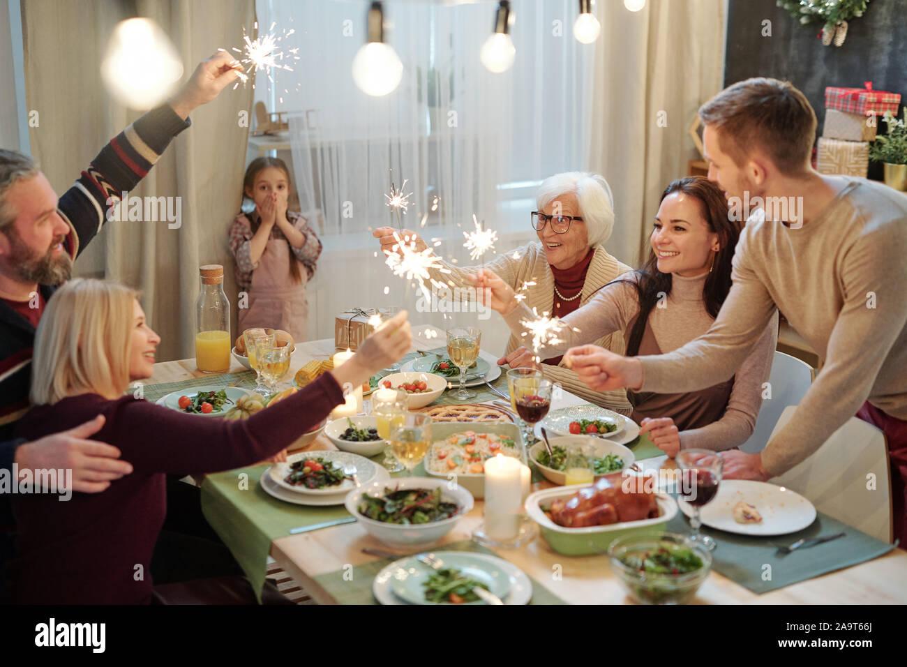 Heureux les jeunes et les adultes avec des feux de Bengale assis par table servi Banque D'Images