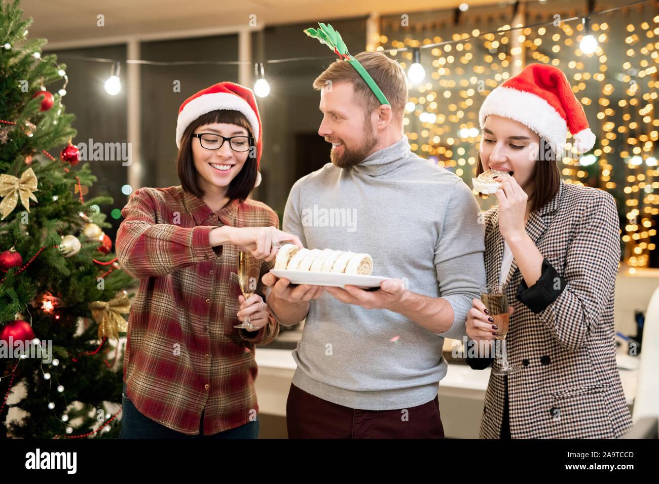 Heureux les jeunes femmes d'affaires en bénéficiant d'un dessert et Santa caps champagne Banque D'Images