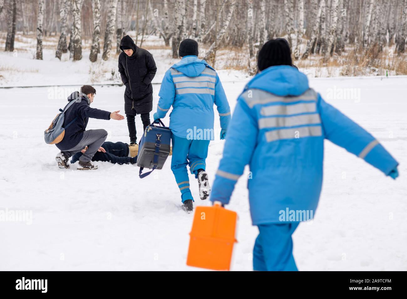 Vue arrière de paramédics en uniforme bleu se dépêchant pour personne malade allongé dans la neige Banque D'Images