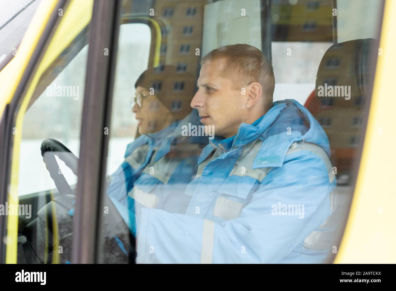 Jeune conducteur de voiture ambulance tout en se dépêchant de direction pour sauver personne malade Banque D'Images