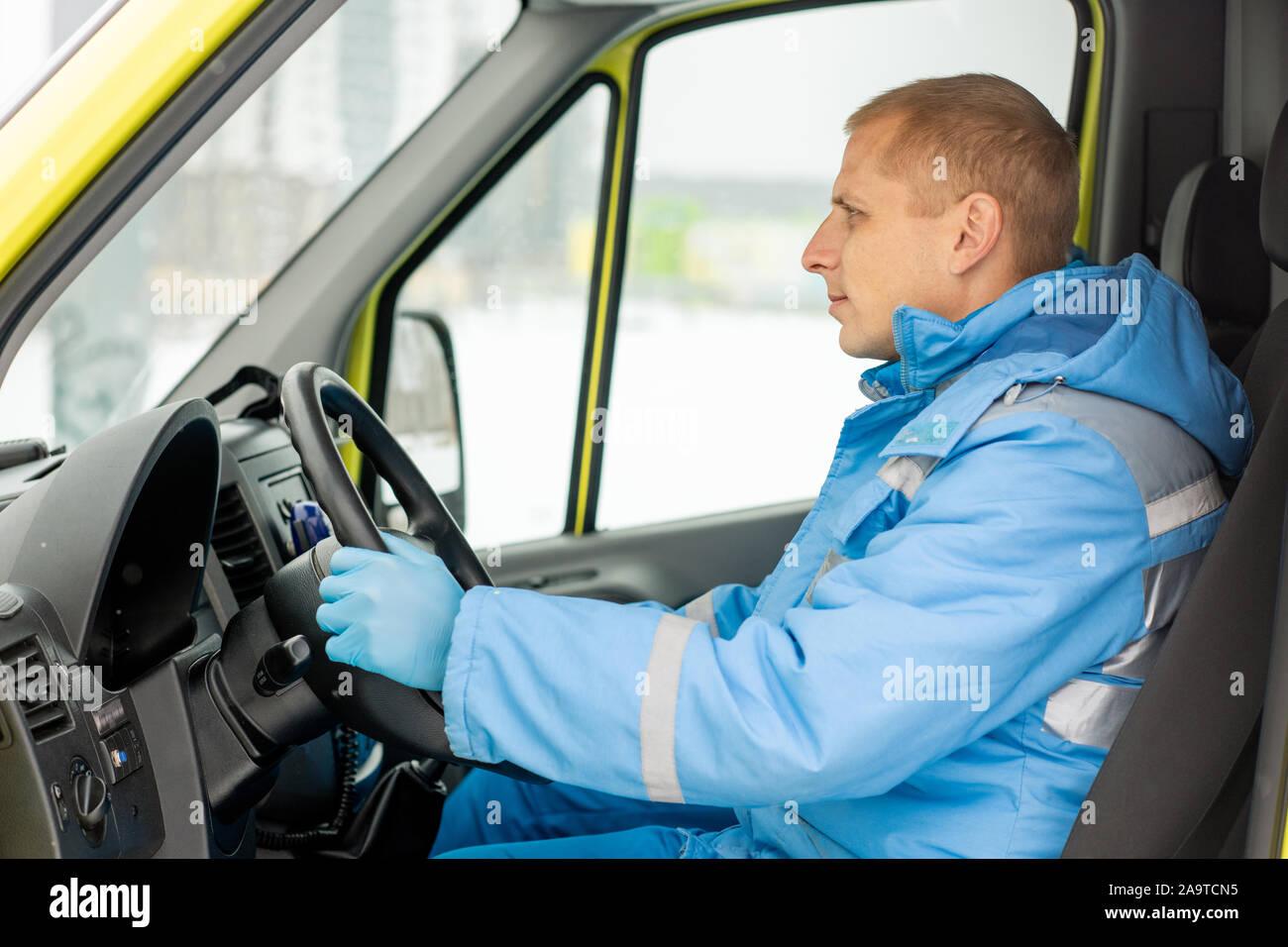 Conducteur de voiture ambulance grave assis par steer en attendant les ambulanciers Banque D'Images