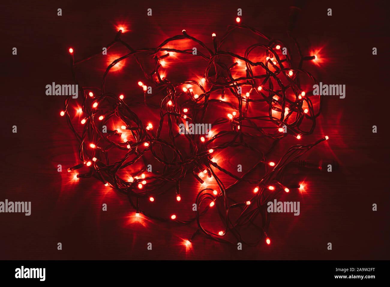 Lumières de Noël rouge sur une table en bois. Rouge vif brillant. Désorganisé led rouge s'allume. Banque D'Images