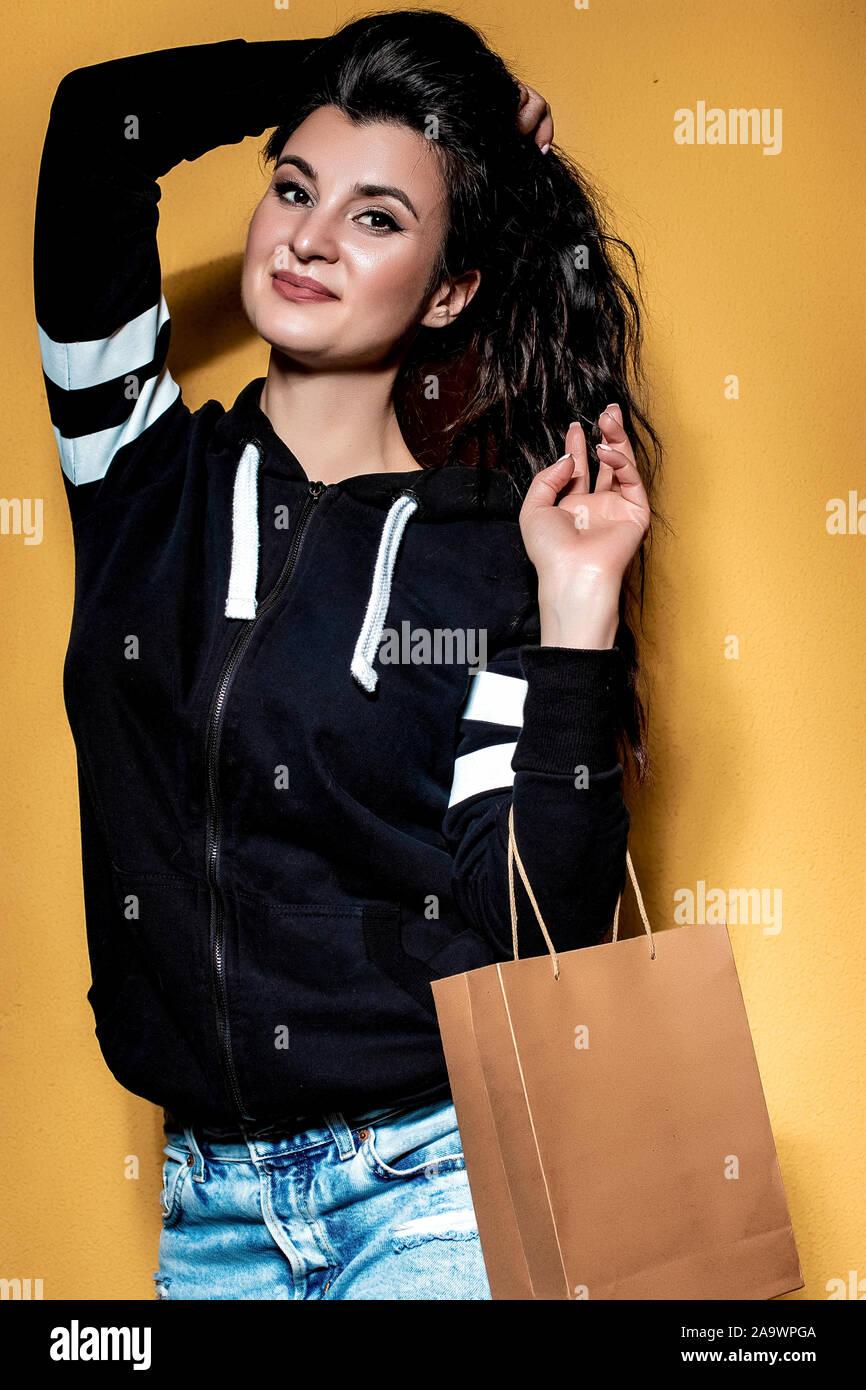 Happy brunette girl est titulaire d'un achat dans un sac d'artisanat sur fond orange. Banque D'Images