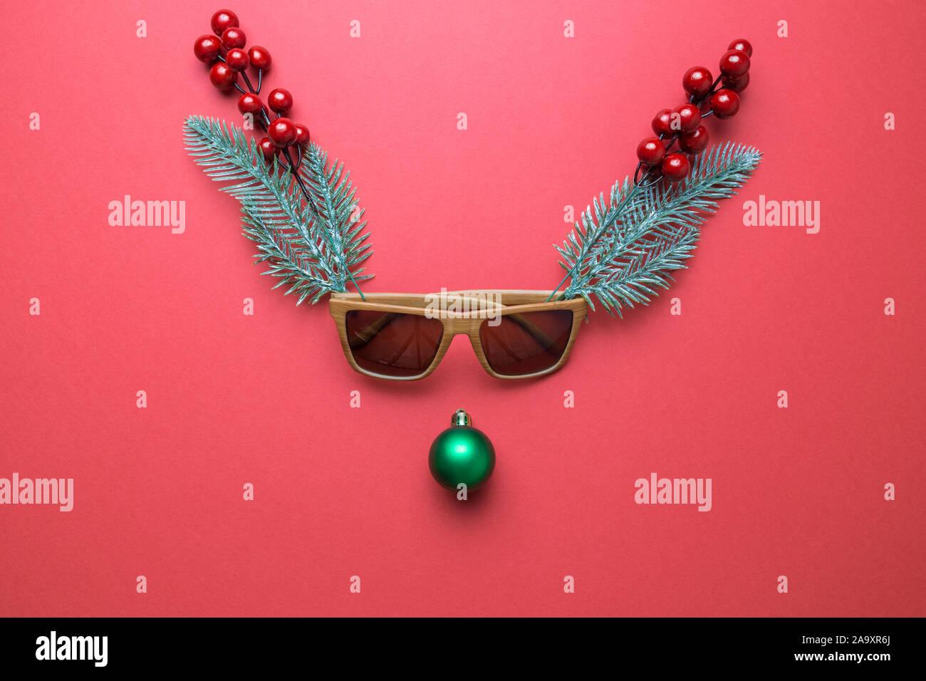 Le renne face en décorations de Noël, des lunettes, des baies de houx et des branches de pins. Concept minimal. Mise à plat Banque D'Images