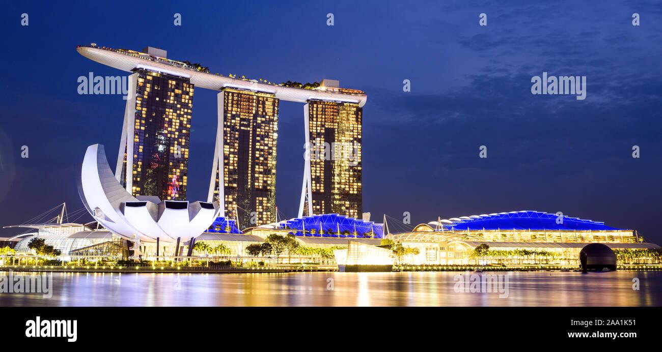 Vue imprenable sur la Marina Bay skyline avec de beaux gratte-ciels illuminés au cours d'un splendide coucher de soleil à Singapour. Banque D'Images