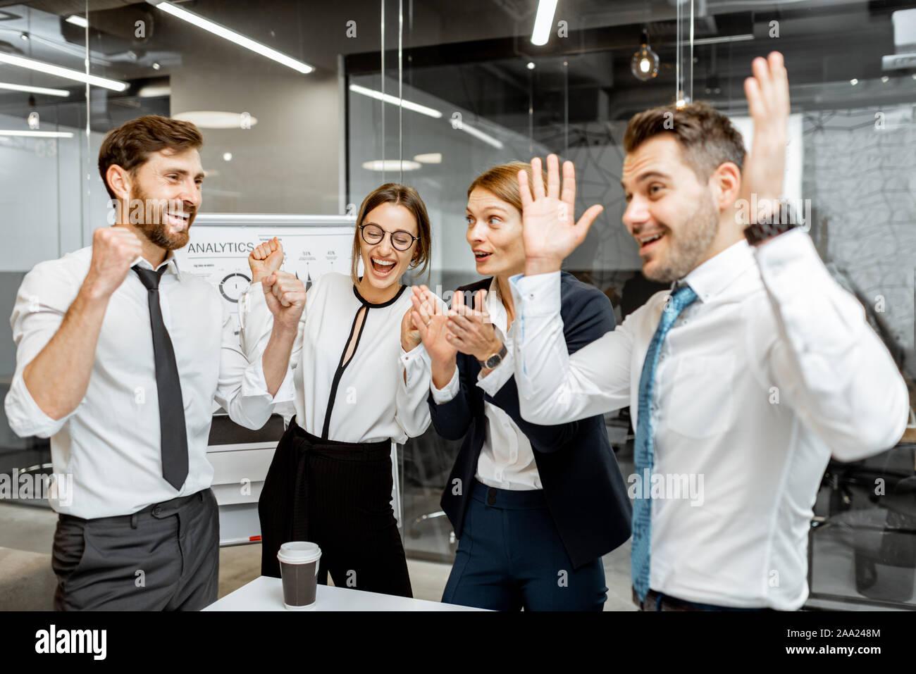 Les employés de l'entreprise réussie se sentir excité avec une bonne performance financière, difficile de travailler ensemble dans la salle de réunion Banque D'Images