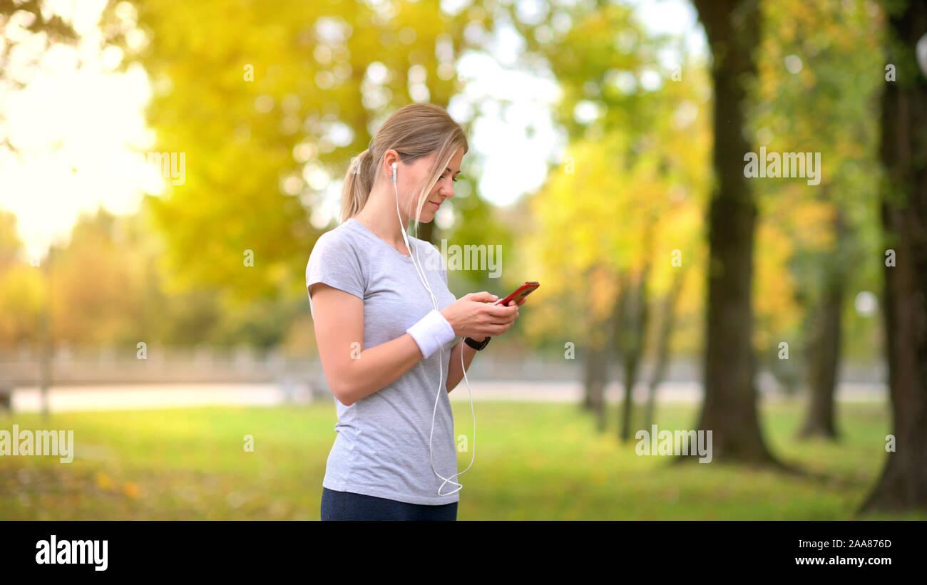 Athlète fille jogging dans le parc le soir. Se reposer et parler sur les réseaux sociaux. Écouter de la musique. D'entraînement. Mode de vie sain. Banque D'Images