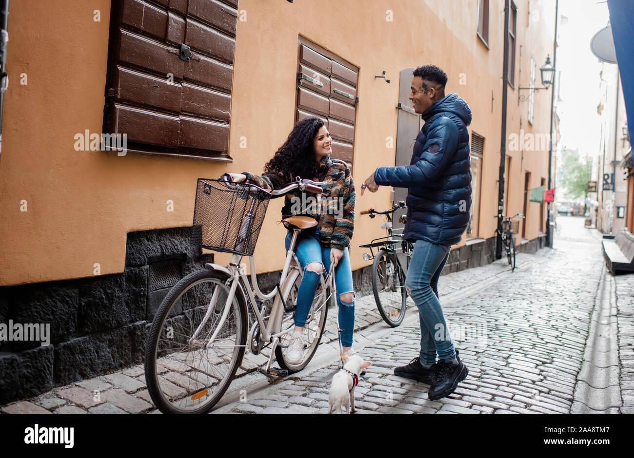 L'homme et de la femme dans la rue en Europe sam parler sur un vélo push Banque D'Images