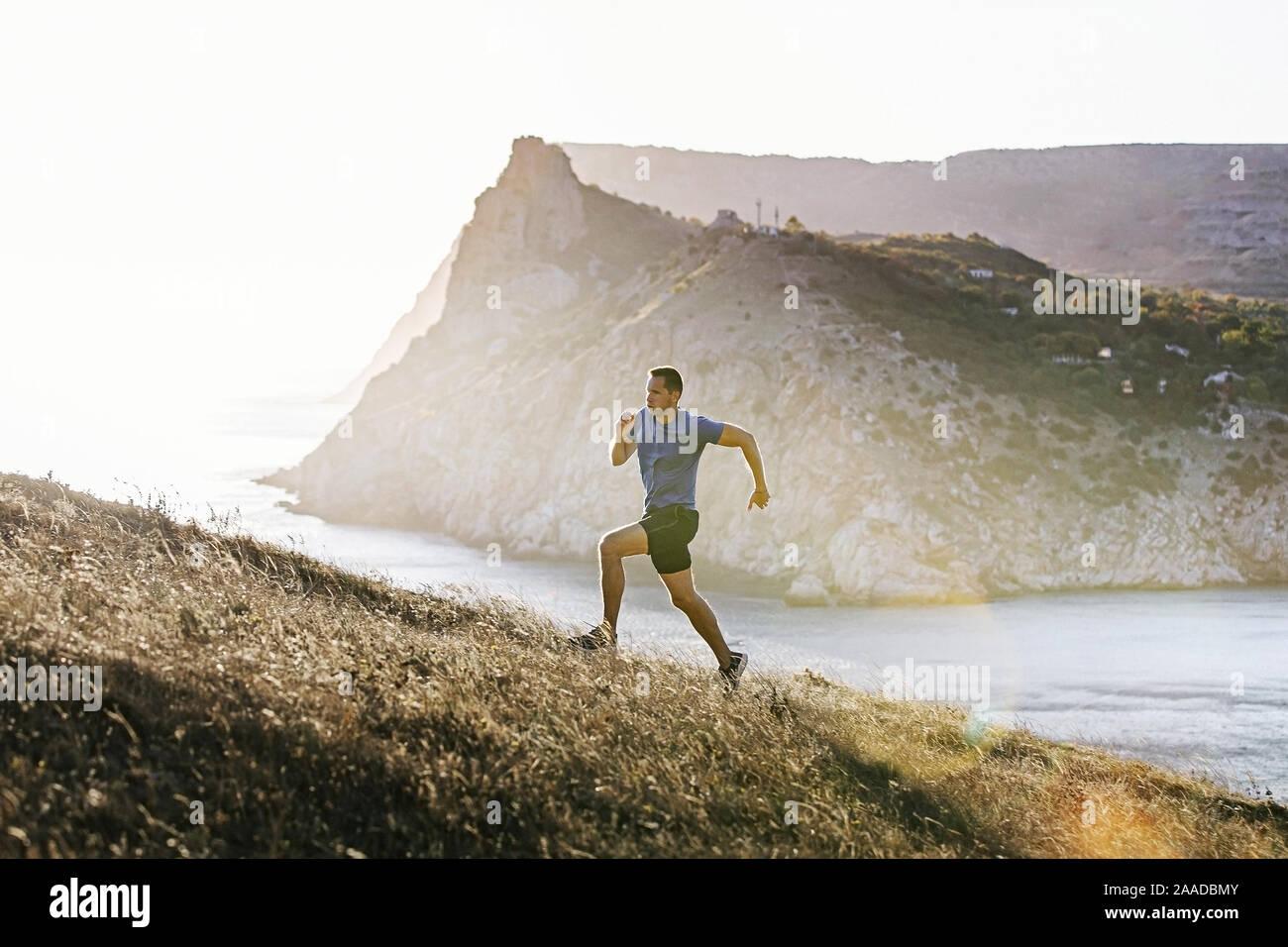 L'homme sportif sous mountain trail dans la pente au coucher du soleil et de la lumière du soleil Banque D'Images